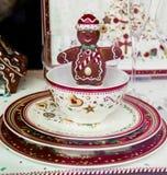Peu d'homme de chocolat souriant dans la tasse de porcelaine des plats de porcelaine photo stock