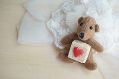 Peu d'ours avec le cube en sucre décoré par peu de coeur rouge sur le pas Photo libre de droits