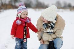 Peu de bébé de l'hiver et sa jeune mère Image stock