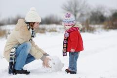 Peu de bébé de l'hiver et sa jeune mère Photographie stock libre de droits