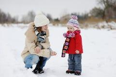 Peu de bébé de l'hiver et sa jeune mère Photos stock