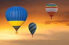 Peu de ballons à air chauds en vol sur le ciel de coucher du soleil Image stock