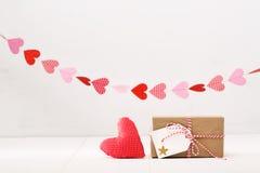 Peu de boîte-cadeau avec des coeurs accrochant en haut Photo stock