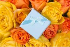 Peu de boîte-cadeau bleu et beau bouquet des roses Image stock