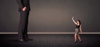 Peu de bussineswoman devant un concept de jambes de patron de géant Image libre de droits