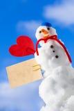 Peu de carte de papier de coeur rouge de bonhomme de neige de Noël heureux extérieure. Hiver. Photos stock