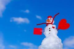 Peu de carte de papier de coeur rouge de bonhomme de neige de Noël heureux extérieure. Hiver. Images stock