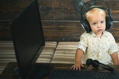 Peu de casque de bluetooth d'usage d'enfant à communiquer Le garçon écoutent casque utilisant l'informatique Vrais articles durs images stock