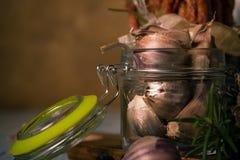 Peu de clous de girofle d'ail dans le pot en verre à côté de la brindille de romarin Images libres de droits
