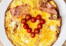 Peu de coeur fait de tomates-cerises sur le jambon et les oeufs pour val Photos libres de droits
