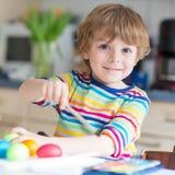 Peu de coloration de garçon d'enfant eggs pour des vacances de Pâques Images stock