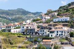 Peu de construction de village contre une pente de montagne à l'île de la Madère Images libres de droits
