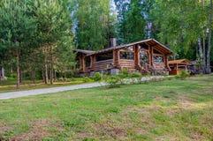 Peu de cottage moderne de rondin dans un bel emplacement tranquille sur le fond des pins Photo stock