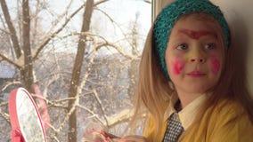 Peu de fille appliquer le maquillage pour le carnaval sur son visage banque de vidéos