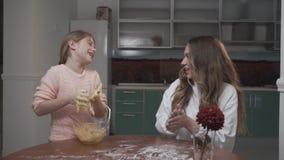 Peu de fille apprend comment faire cuire à la maison La préparation d'enfant ont la pâte collante sur des mains banque de vidéos