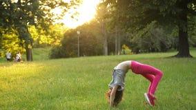 Peu de fille ayant l'amusement sur l'herbe verte tout en faisant une roue acrobatique Le jeune enfant sportif a une humeur vraime banque de vidéos