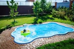 Peu de fille d'amusement est piscine Photo stock
