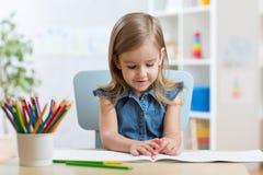 Peu de fille d'enfant dessine se reposer à la table dans la chambre dans la crèche images stock