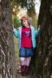 Peu de fille de gingembre se tenant entre les arbres Photographie stock libre de droits