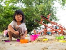 Peu de fille de l'Asie s'asseyant dans le bac à sable et jouant avec le seau de pelle à sable de jouet Photo stock