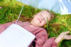 Peu de fille est tombée endormi avec un livre en parc sur l'herbe photographie stock