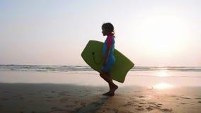 Peu de fille marche le long de la plage de sable d'océan avec la planche de surf au coucher du soleil banque de vidéos