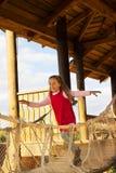Peu de fille mignonne d'école dans la robe rouge ayant l'amusement et jouer extérieurs dans le jour d'été Photos libres de droits