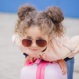 Peu de fille de sourire bouclée de hippie de mode dans des lunettes de soleil s'étendant sur la valise Voyage de concept Image stock