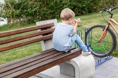 Peu de garçon bouleversé blond dans des jeans occasionnels seul portent se reposer sur le banc en bois en parc Enfant malheureux  image libre de droits