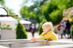 Peu de garçon de cheveux blonds jouant avec la fontaine de ville le jour ensoleillé d'été photographie stock libre de droits