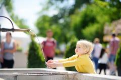 Peu de garçon de cheveux blonds jouant avec la fontaine de ville le jour ensoleillé d'été photos stock