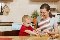 Peu de garçon d'enfant aide la mère à faire cuire le biscuit de gingembre Maman et enfant heureux de famille dans le matin de wee Photo stock
