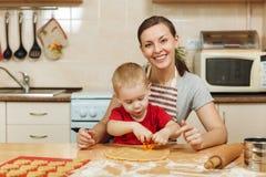 Peu de garçon d'enfant aide la mère à faire cuire le biscuit de gingembre Maman et enfant heureux de famille dans le matin de wee Photos libres de droits