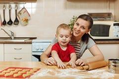 Peu de garçon d'enfant aide la mère à faire cuire le biscuit de gingembre Maman et enfant heureux de famille dans le matin de wee Photographie stock