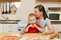 Peu de garçon d'enfant aide la mère à faire cuire le biscuit de gingembre Maman et enfant heureux de famille dans le matin de wee Photos stock