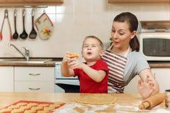 Peu de garçon d'enfant aide la mère à faire cuire le biscuit de gingembre Maman et enfant heureux de famille dans le matin de wee Photographie stock libre de droits