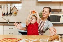 Peu de garçon d'enfant aide la mère à faire cuire le biscuit de gingembre Maman et enfant heureux de famille dans le matin de wee Image stock