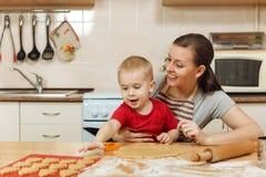 Peu de garçon d'enfant aide la mère à faire cuire le biscuit de gingembre Maman et enfant heureux de famille dans le matin de wee Images libres de droits