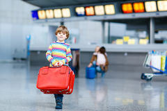 Peu de garçon d'enfant avec des valises sur l'aéroport international Photo libre de droits