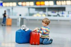 Peu de garçon d'enfant avec des valises sur l'aéroport international Photos libres de droits