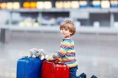 Peu de garçon d'enfant avec des valises sur l'aéroport international Image libre de droits