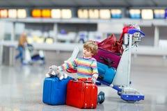Peu de garçon d'enfant avec des valises sur l'aéroport international Photographie stock libre de droits