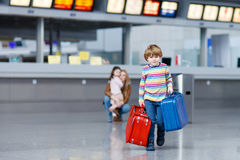 Peu de garçon d'enfant avec des valises sur l'aéroport international Image stock