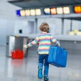 Peu de garçon d'enfant avec des valises sur l'aéroport international Photographie stock