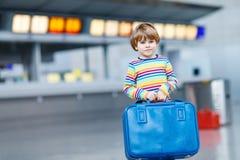 Peu de garçon d'enfant avec des valises sur l'aéroport international Photos stock