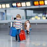 Peu de garçon d'enfant avec des valises sur l'aéroport international Photo stock
