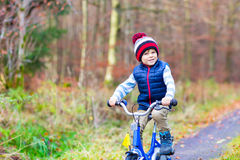 Peu de garçon d'enfant avec la bicyclette dans la forêt d'automne Photos libres de droits