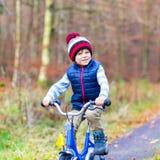Peu de garçon d'enfant avec la bicyclette dans la forêt d'automne Images stock