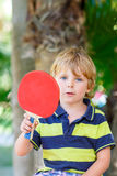 Peu de garçon d'enfant avec la raquette de ping-pong Photos stock