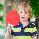 Peu de garçon d'enfant avec la raquette de ping-pong Images libres de droits